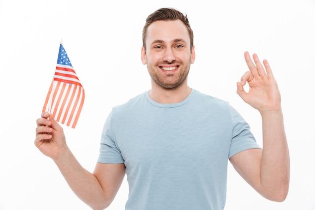 Radosny młody człowiek w swobodnej koszulce trzyma małą amerykańską flagę i gestykuluje ok znak