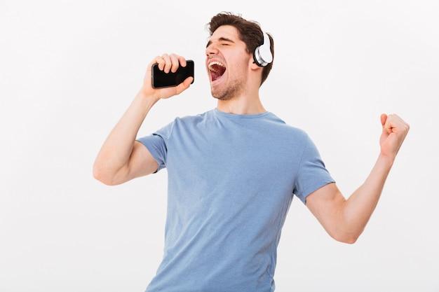 Radosny młody człowiek w wieku 30 lat w swobodnej koszulce słuchający muzyki za pomocą bezprzewodowych słuchawek i śpiewający za pomocą smartfona jak mikrofon, odizolowane na białej ścianie