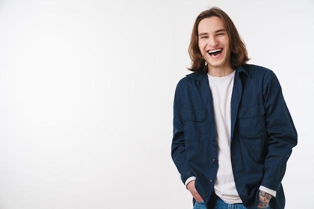 Radosny młody człowiek z długimi włosami śmiejący się i patrzący na przód izolowany nad białą ścianą