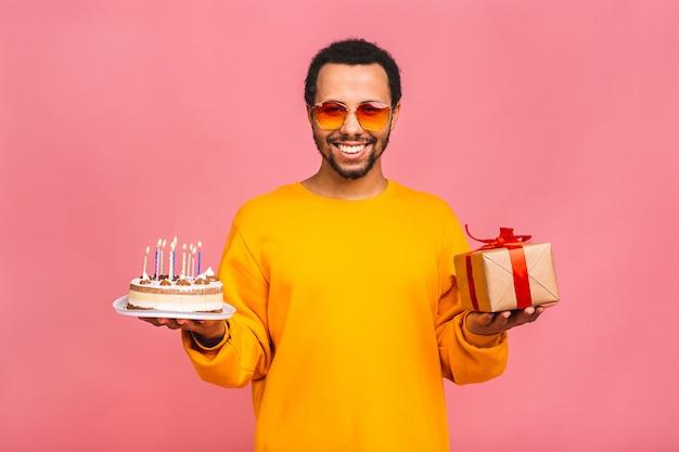 Radosny młody człowiek z pudełko dmuchanie świeczki na tort urodzinowy na różowym tle.