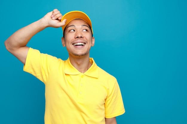 Radosny młody dostawca ubrany w mundur i czapkę chwytający czapkę patrząc w róg