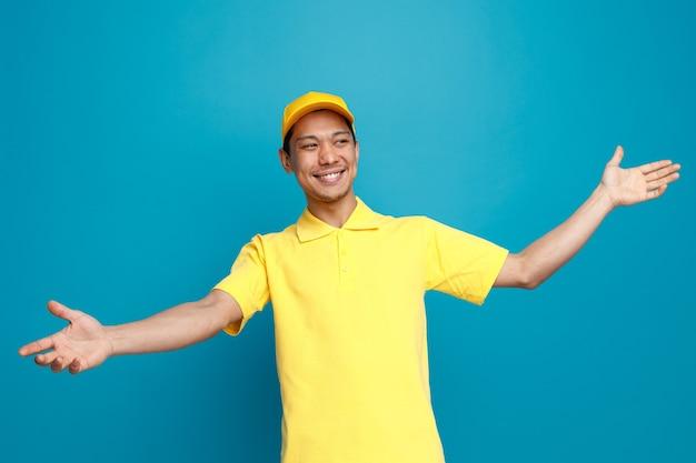 Radosny Młody Dostawca Ubrany W Mundur I Czapkę Patrząc Na Bok Wyciągając Ręce Pokazując Puste Ręce Premium Zdjęcia
