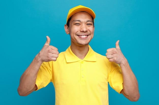 Radosny młody dostawca ubrany w mundur i czapkę pokazując kciuki do góry