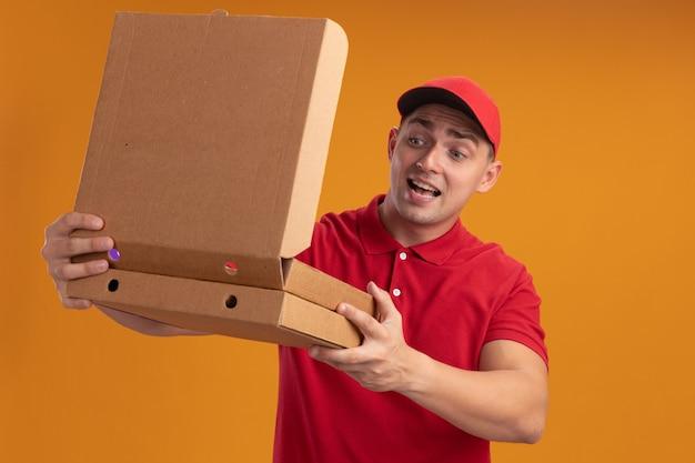 Radosny młody dostawca ubrany w mundur z otwarciem czapki i patrząc na pudełko po pizzy na białym tle na pomarańczowej ścianie