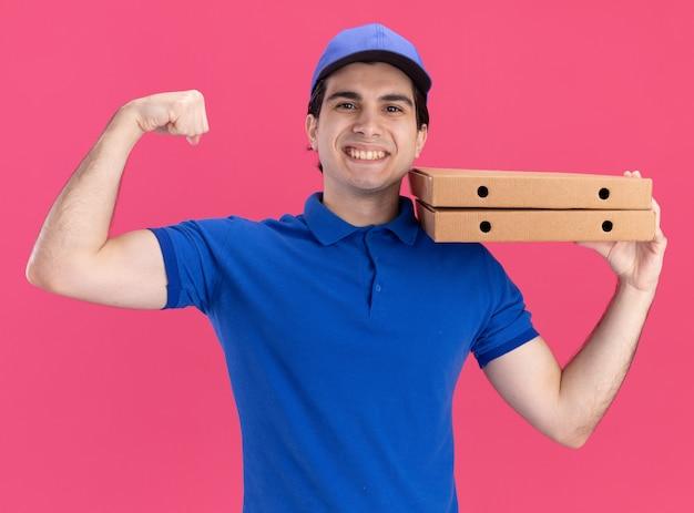 Radosny młody dostawca w niebieskim mundurze i czapce trzymający paczki z pizzą na ramieniu, patrzący z przodu, wykonujący silny gest na różowej ścianie