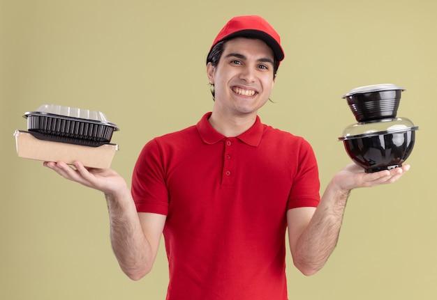 Radosny młody kaukaski dostawca w czerwonym mundurze i czapce, trzymający pojemniki na żywność i papierowe opakowanie żywności