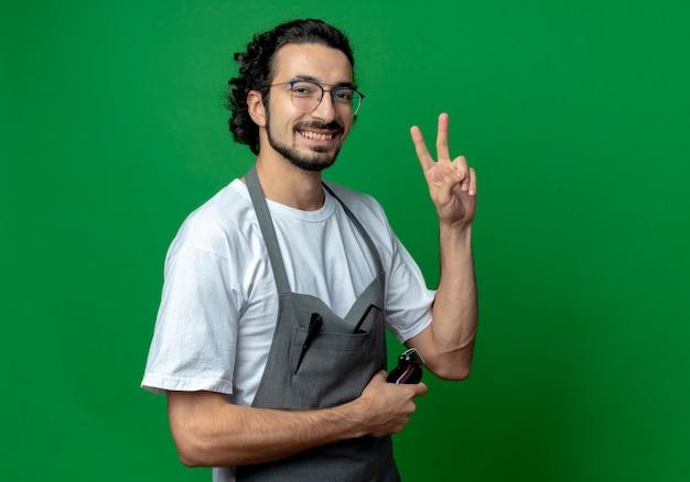 Radosny młody kaukaski fryzjer męski w okularach i falującej opasce do włosów w mundurze trzymając maszynkę do strzyżenia włosów i robiący znak pokoju na białym tle na zielonym tle z miejsca na kopię