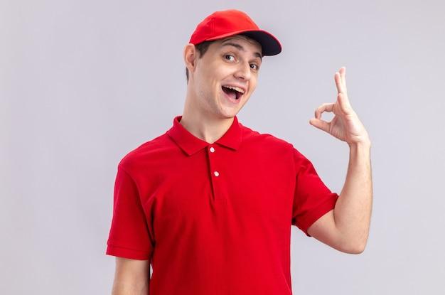 Radosny młody kaukaski mężczyzna dostawy w czerwonej koszuli, wskazując znak ok