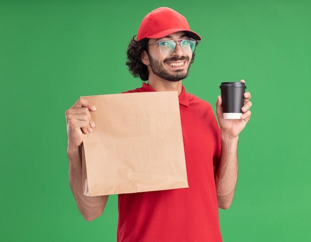 Radosny młody kaukaski mężczyzna dostawy w czerwonym mundurze i czapce w okularach trzymających papierową paczkę i plastikową filiżankę kawy na zielonej ścianie