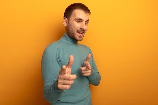Radosny młody kaukaski mężczyzna patrząc na kamery mrugając, robi ci gest na białym tle na pomarańczowym tle z miejsca na kopię