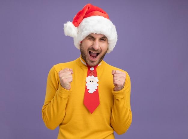 Radosny młody kaukaski mężczyzna ubrany w świąteczny kapelusz i krawat, mrugający, robi gest tak na białym tle na fioletowej ścianie z miejsca na kopię
