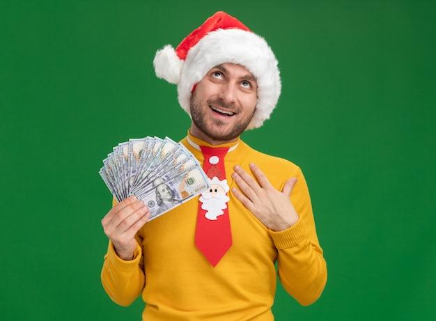 Radosny młody kaukaski mężczyzna ubrany w świąteczny kapelusz i krawat trzymając pieniądze, kładąc rękę na piersi patrząc w górę na białym tle na zielonym tle