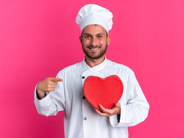 Radosny młody kucharz kaukaski w mundurze szefa kuchni i czapce, patrząc na aparat trzymający i wskazujący na kształt serca na różowej ścianie