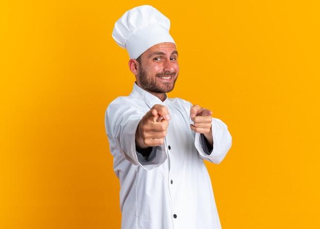 Radosny młody kucharz kaukaski w mundurze szefa kuchni i czapce robi gest