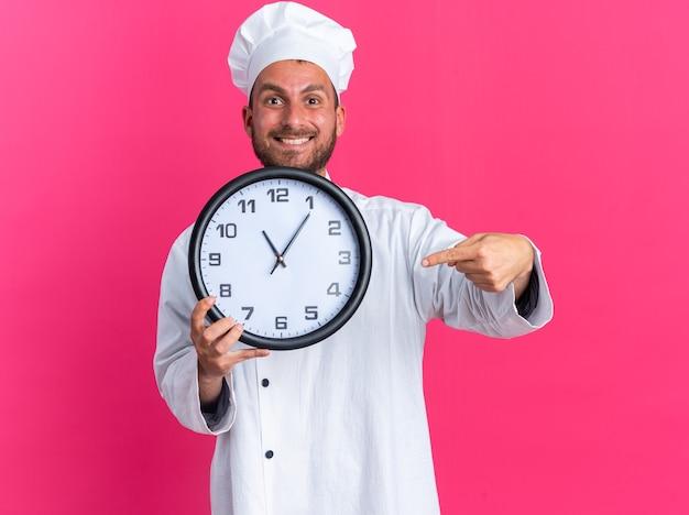 Radosny młody kucharz rasy kaukaskiej w mundurze szefa kuchni i czapce pokazujący zegar wskazujący na niego