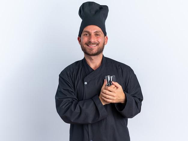 Radosny młody kucharz rasy kaukaskiej w mundurze szefa kuchni i czapce trzymający szklankę wody przed sercem