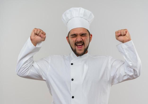 Radosny młody kucharz w mundurze szefa kuchni, podnoszący pięści z zamkniętymi oczami na białym tle na białej ścianie