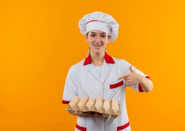 Radosny młody ładny kucharz w mundurze szefa kuchni z szelkami na zęby, trzymając i wskazując na karton jaj na białym tle na pomarańczowej przestrzeni