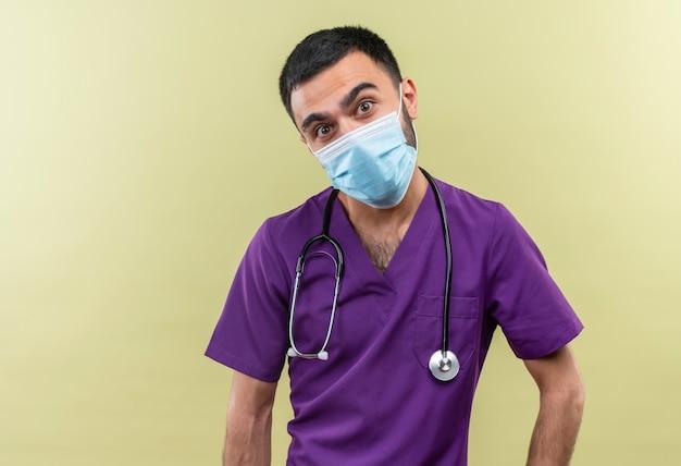 Radosny młody lekarz mężczyzna ubrany w fioletową odzież chirurga i maskę medyczną stetoskop na odizolowanej zielonej ścianie