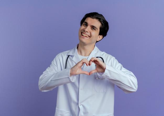 Radosny młody lekarz mężczyzna ubrany w szlafrok i stetoskop robi znak serca na białym tle na fioletowej ścianie z miejsca na kopię