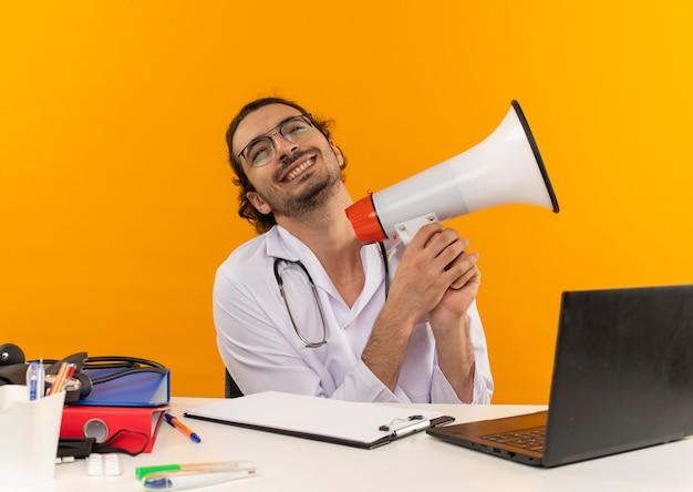 Radosny młody lekarz mężczyzna z okularami medycznymi w szlafroku medycznym ze stetoskopem siedzący przy biurku pracuje na laptopie z narzędziami medycznymi trzymającymi głośnik na izolowanym żółtym tle z miejscem na kopię