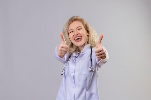 Radosny młody lekarz ubrany w stetoskop w sukni medycznej kciuki do góry na białej ścianie