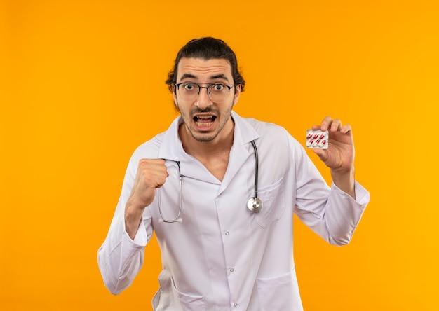 Radosny młody lekarz z okularami medycznymi na sobie szlafrok medyczny ze stetoskopem, trzymając pigułki i pokazując gest tak