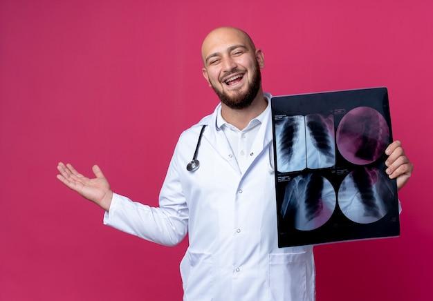Radosny młody łysy lekarz ubrany w szlafrok medyczny i stetoskop, trzymając rentgen i rozłożoną rękę
