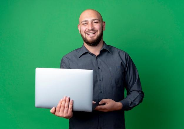Radosny młody łysy mężczyzna call center gospodarstwa laptopa na białym tle na zielono