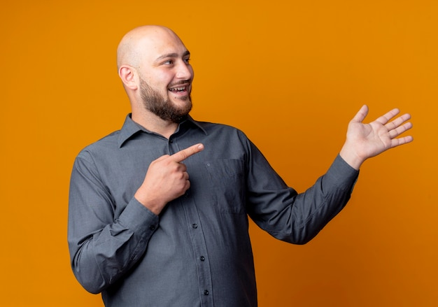 Radosny młody łysy mężczyzna call center patrząc i wskazując na bok i pokazując pustą rękę na białym tle na pomarańczowo