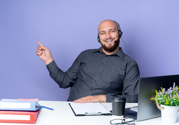 Radosny młody łysy mężczyzna call center sobie zestaw słuchawkowy siedzi przy biurku z narzędzi pracy, wskazując na bok na białym tle na fioletowo