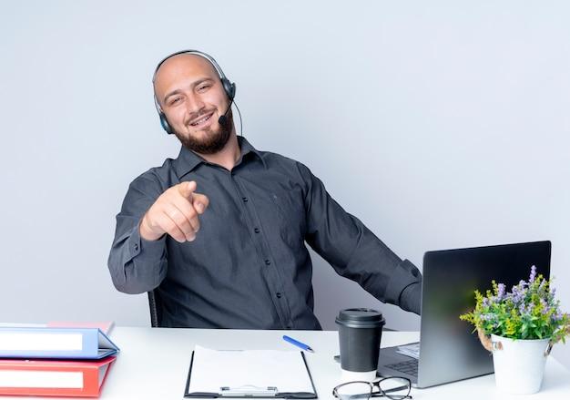 Radosny młody łysy mężczyzna call center sobie zestaw słuchawkowy siedzi przy biurku z narzędzi pracy, wskazując z przodu na białym tle