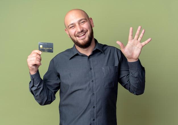 Radosny młody łysy mężczyzna call center trzyma kartę kredytową i pokazuje pięć ręką odizolowane na oliwkowej zieleni