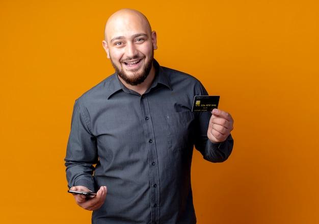 Radosny młody łysy mężczyzna call center trzyma kartę kredytową i telefon komórkowy na pomarańczowym tle