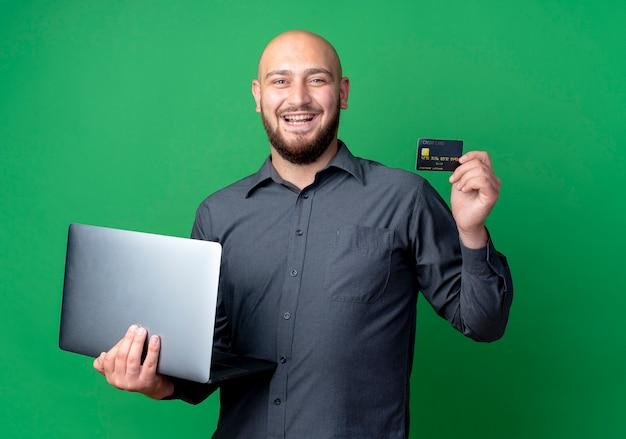 Radosny młody łysy mężczyzna call center trzyma laptop i kartę kredytową na białym tle na zielono