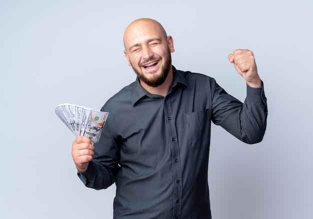 Radosny młody łysy mężczyzna call center trzymając pieniądze i zaciskając pięść z zamkniętymi oczami na białym tle