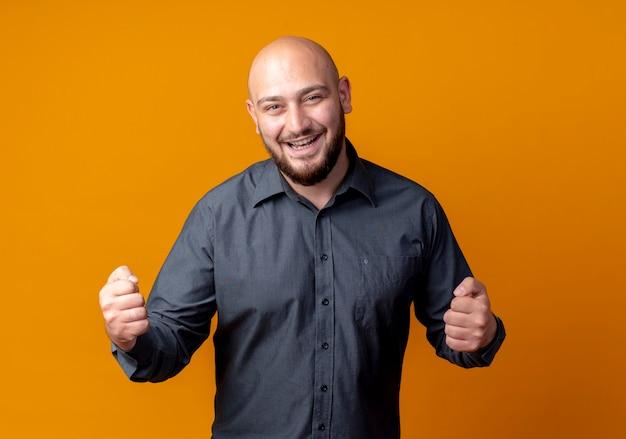Radosny młody łysy mężczyzna call center zaciskając pięści robi tak gest odizolowany na pomarańczowo