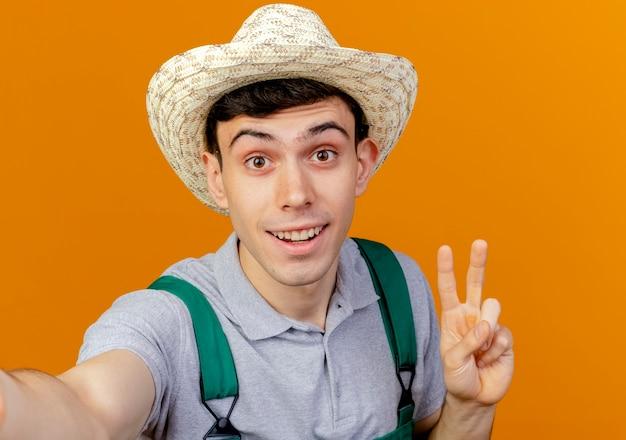 Radosny młody ogrodnik męski w kapeluszu ogrodniczym gestykuluje ręką znak zwycięstwa i udaje, że trzyma aparat