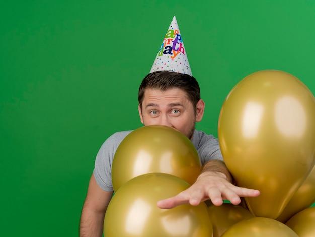 Radosny młody partyjny facet ubrany w czapkę urodzinową stojący za balonami wyciągając rękę na białym tle na zielono