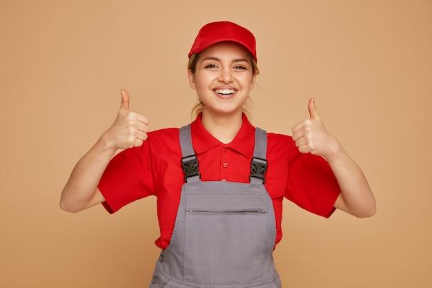 Radosny młody pracownik budowlany noszenia czapki i munduru pokazując kciuki do góry