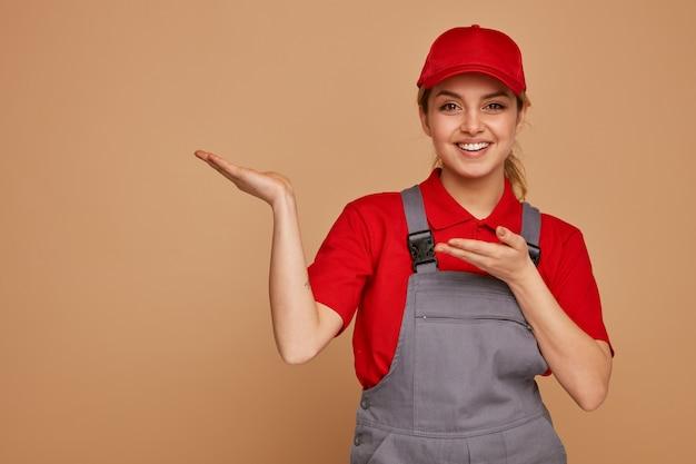 Radosny młody pracownik budowlany noszenia czapki i munduru, wskazując na bok rękami