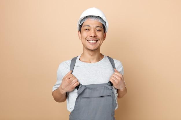 Radosny młody pracownik budowlany w kasku i mundurze, chwytając za mundur