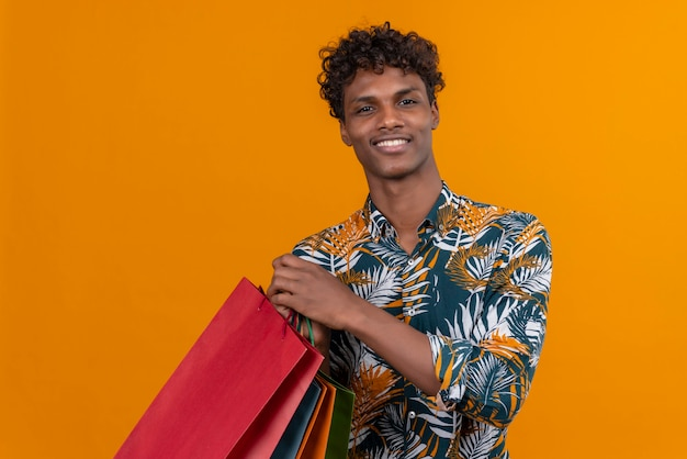 Radosny młody przystojny ciemnoskóry mężczyzna z kręconymi włosami w liściach koszulę z nadrukiem, uśmiechając się, trzymając torby na zakupy, stojąc na pomarańczowym tle