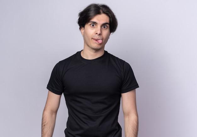 Radosny młody przystojny facet na sobie czarną koszulkę pokazując język na białym tle na białej ścianie