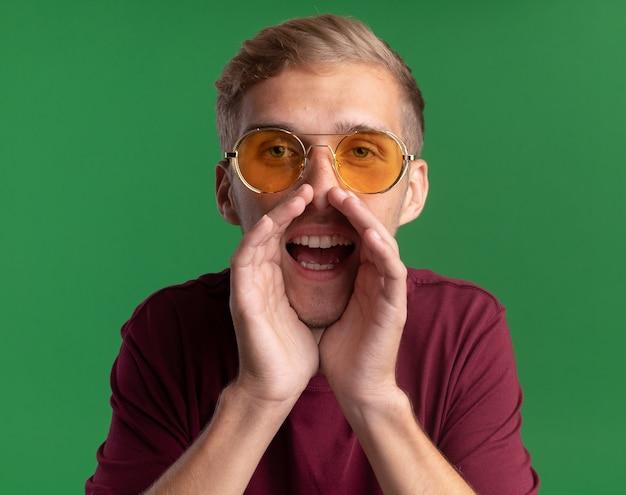 Radosny młody przystojny facet na sobie czerwoną koszulę i okulary - na białym tle na zielonej ścianie
