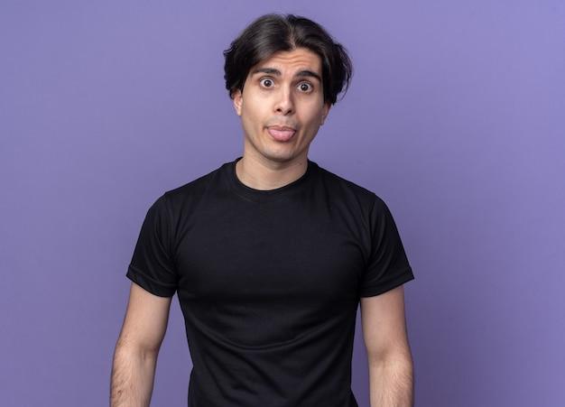 Radosny młody przystojny facet ubrany w czarną koszulkę pokazując język na białym tle na fioletowej ścianie