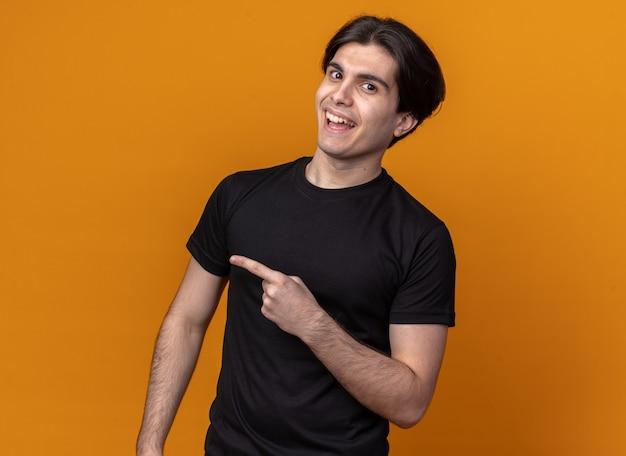 Radosny młody przystojny facet ubrany w czarny t-shirt wskazuje na bok na białym tle na pomarańczowej ścianie z miejsca na kopię