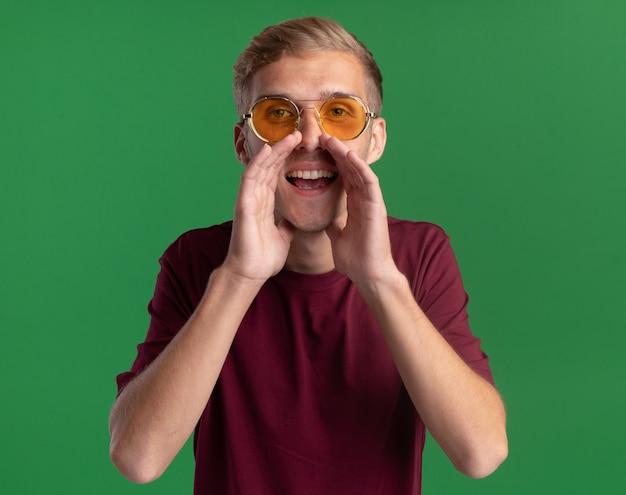 Radosny młody przystojny facet ubrany w czerwoną koszulę i okulary wzywając kogoś na białym tle na zielonej ścianie