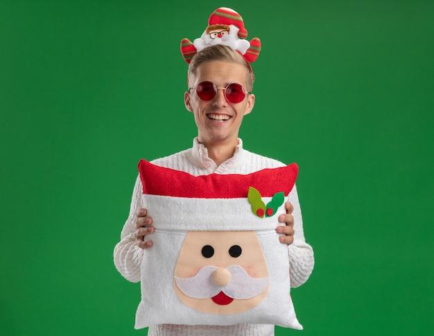 Radosny młody przystojny facet w opasce świętego mikołaja w okularach trzyma poduszkę świętego mikołaja śmiejąc się na białym tle na zielonej ścianie z miejsca na kopię