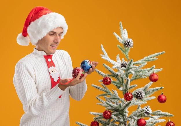 Radosny młody przystojny facet w świątecznej czapce i krawacie świętego mikołaja stojący w pobliżu udekorowanej choinki, trzymając i patrząc na ozdoby choinkowe na białym tle na pomarańczowym tle